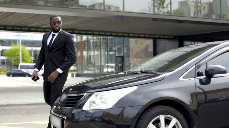 Уверенно Афро-американский человек в деловом костюме приходя к его роскошному автомобилю стоковое изображение rf