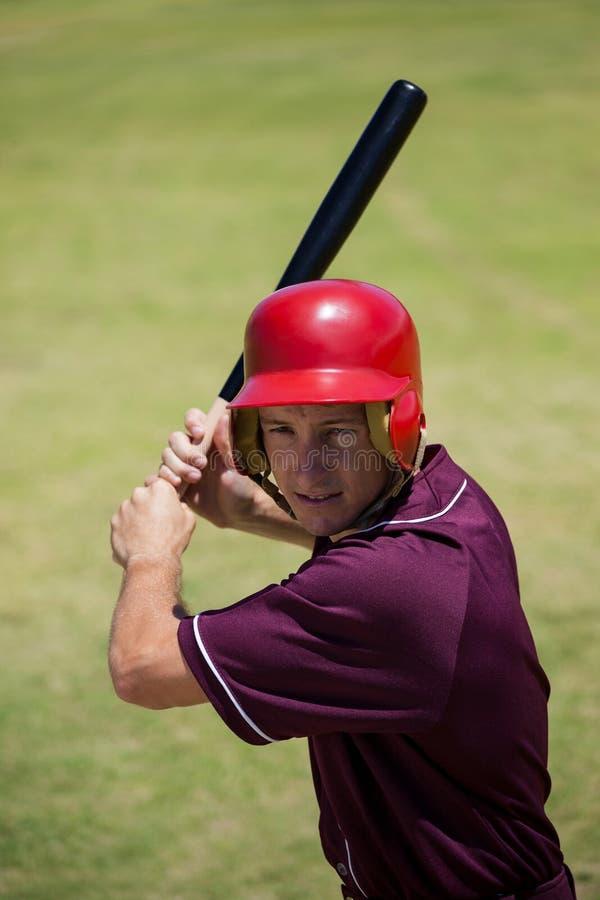Уверенно бейсболист ударяя с летучей мышью стоковые изображения