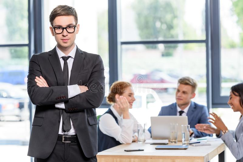 Уверенно бизнесмен перед его коллегами стоковое изображение rf