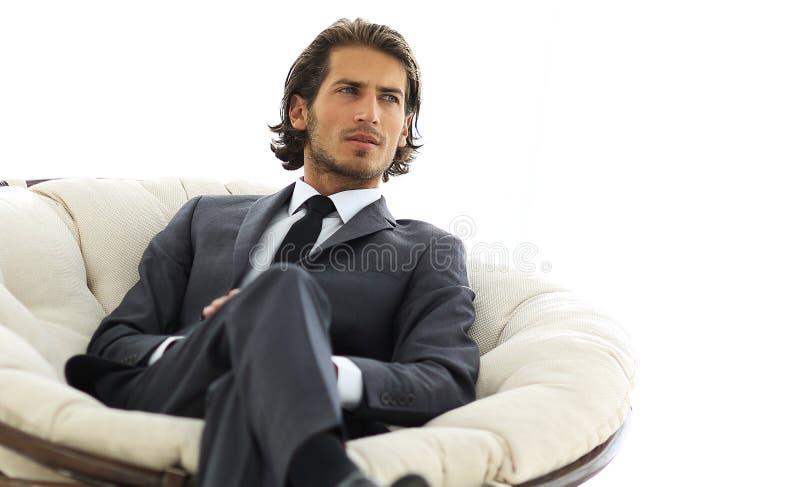 Уверенно бизнесмен сидя в большом удобном стуле стоковые изображения rf