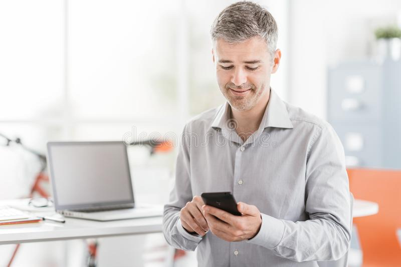 Уверенно бизнесмен сидя на столе офиса и соединяясь с smartphone, он использует apps и работу стоковые изображения