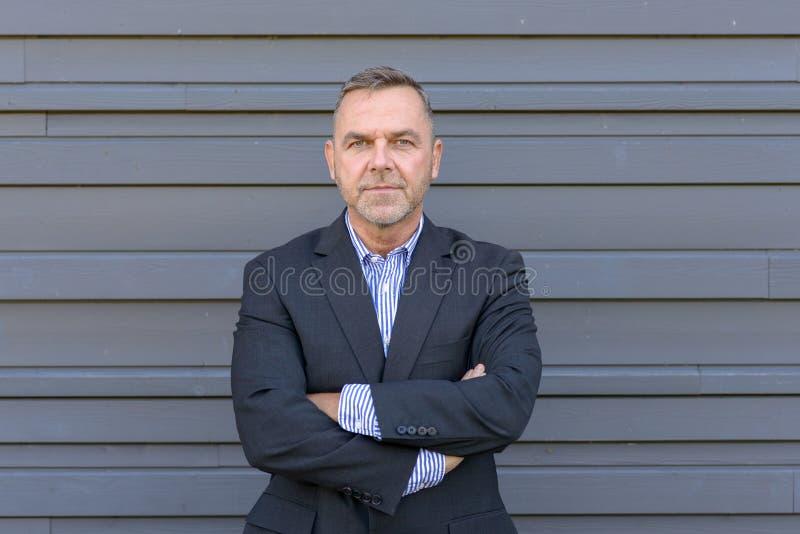 Уверенно бизнесмен среднего возраста над серым цветом стоковая фотография rf