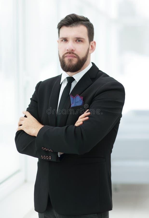 Уверенно бизнесмен стоя около окна офиса стоковые фотографии rf