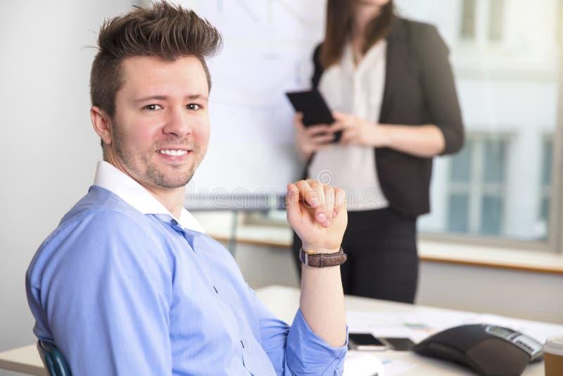 Уверенно бизнесмен усмехаясь пока коллега держа Com таблетки стоковое изображение
