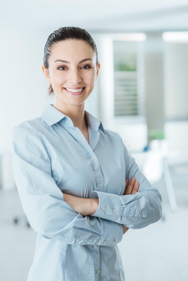 Уверенно бизнес-леди представляя при пересеченные оружия стоковое изображение