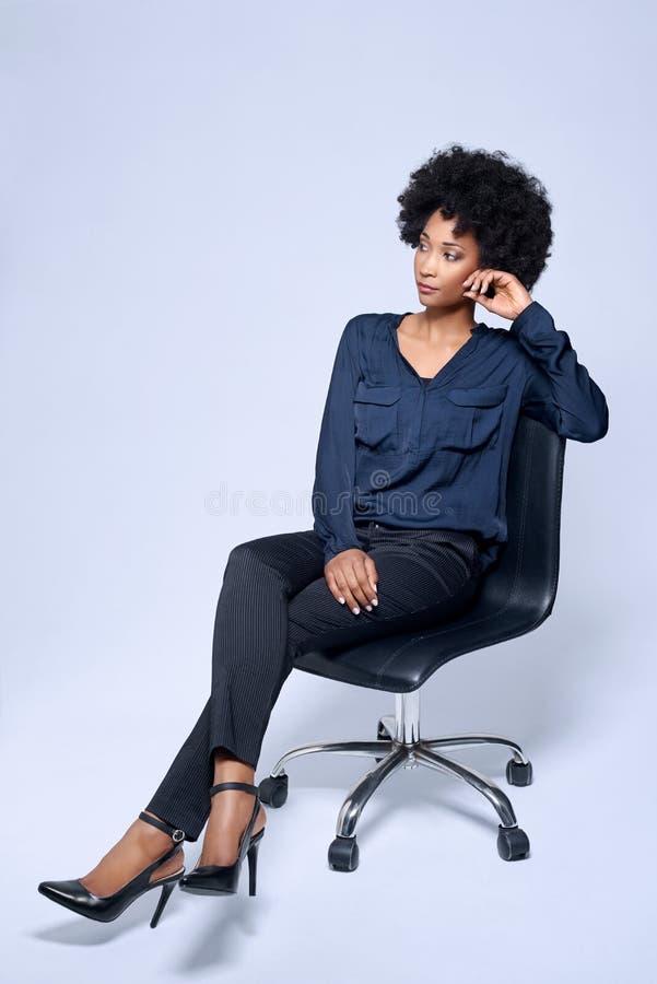 Уверенно бизнес-леди сидя в студии стоковые фото