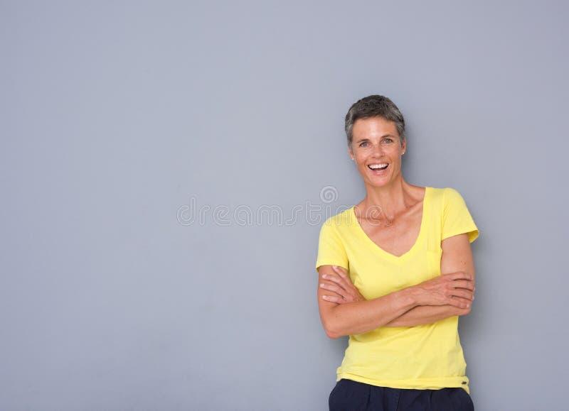 Уверенно более старая женщина усмехаясь против серой предпосылки стоковые изображения rf
