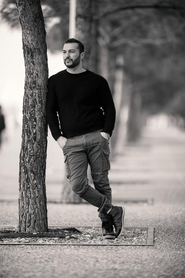 Уверенно грубый красивый представлять человека, полагаясь против дерева стоковое изображение rf
