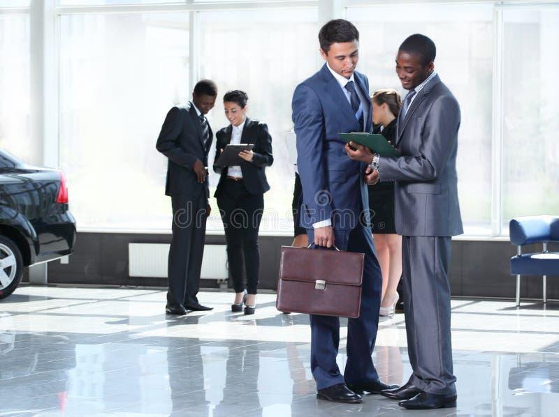 Уверенно деловые партнеры работая в офисе и говорить стоковые фото