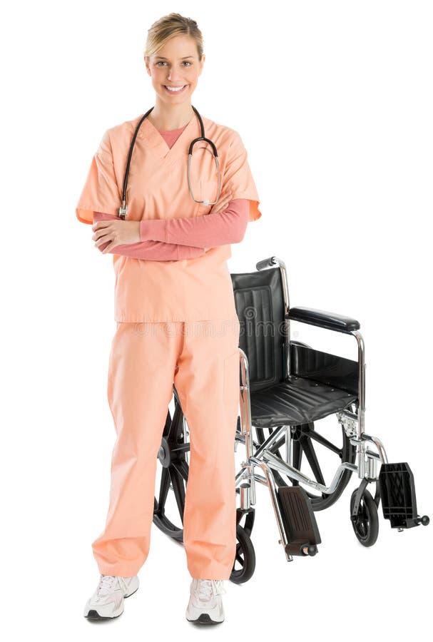 Уверенно женская медсестра усмехаясь пока готовящ кресло-коляску стоковое изображение rf