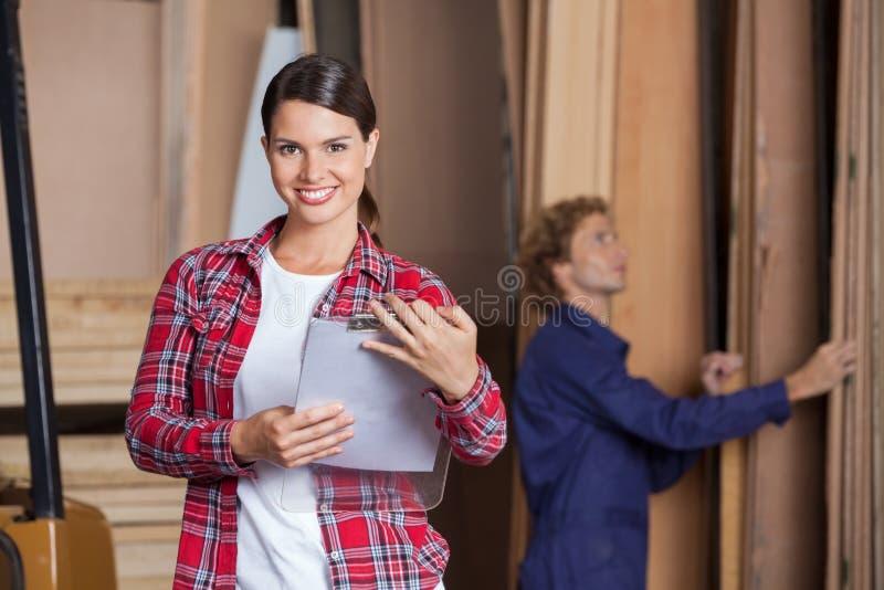 Уверенно женский заведущая держа доску сзажимом для бумаги стоковая фотография