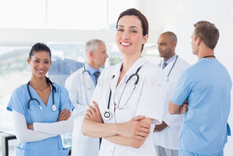 Уверенно женский доктор усмехаясь на камере с ее командой позади стоковая фотография