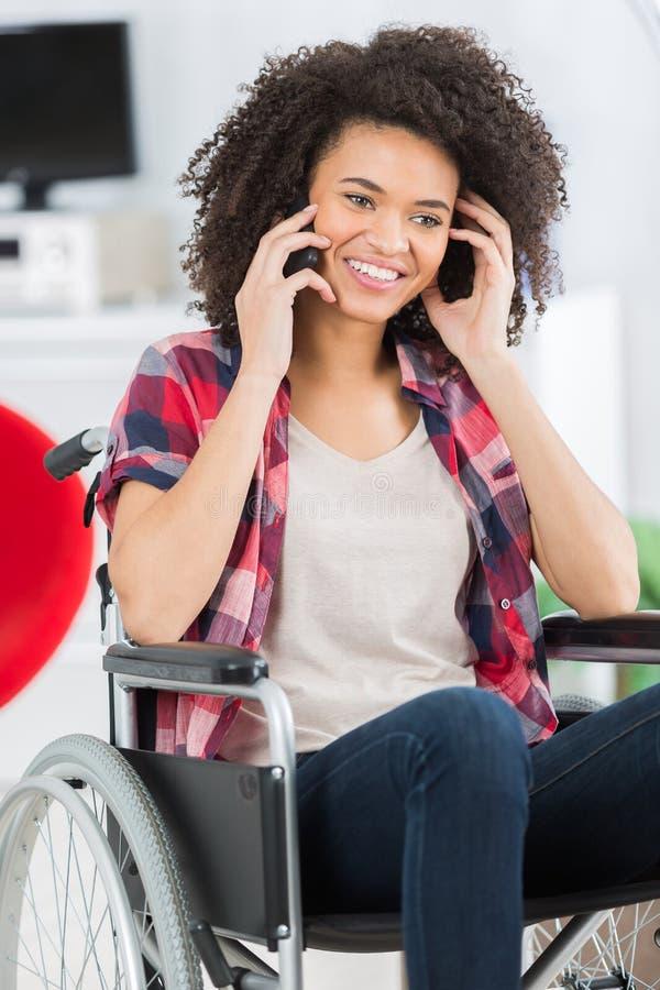 Уверенно женщина в кресло-коляске с мобильным телефоном стоковое изображение rf