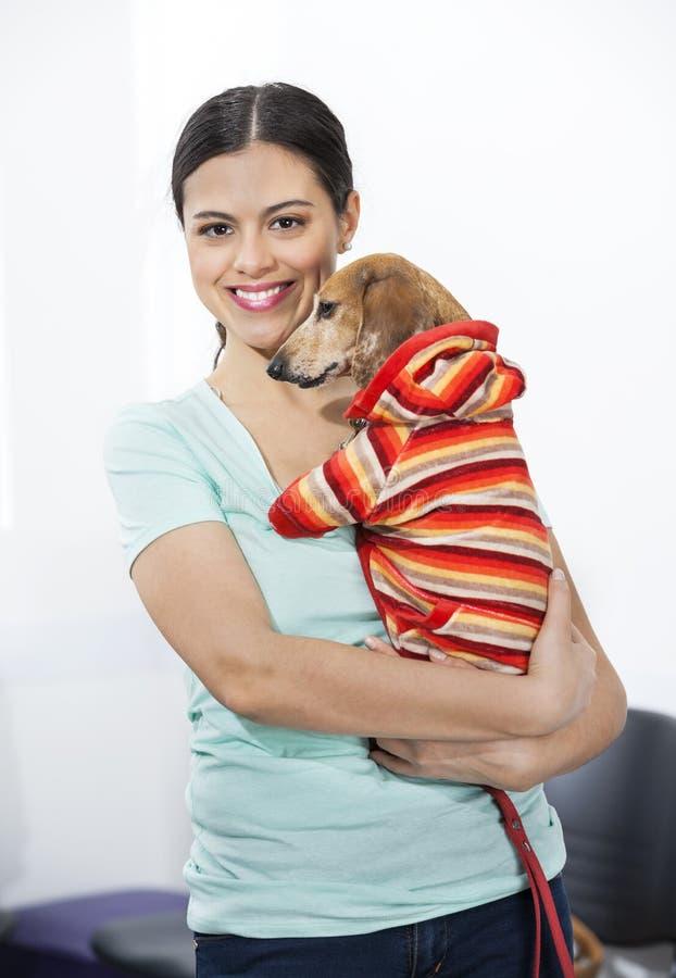Уверенно женщина нося больную таксу в клинике стоковые фотографии rf