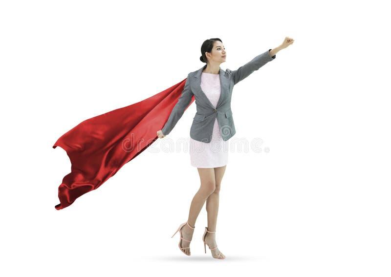 Уверенно женщина супергероя дела нося красную накидку против стоковое фото