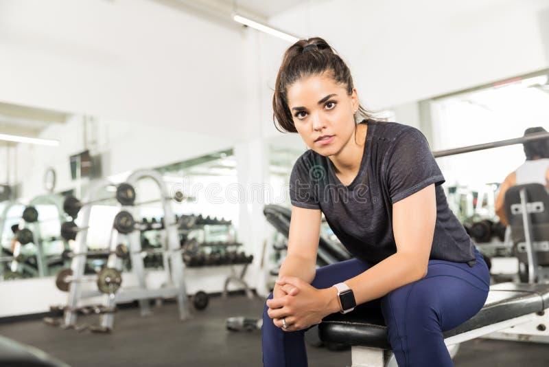 Уверенно женщина с руками сжимала ослаблять на стенде на спортзале стоковое фото rf