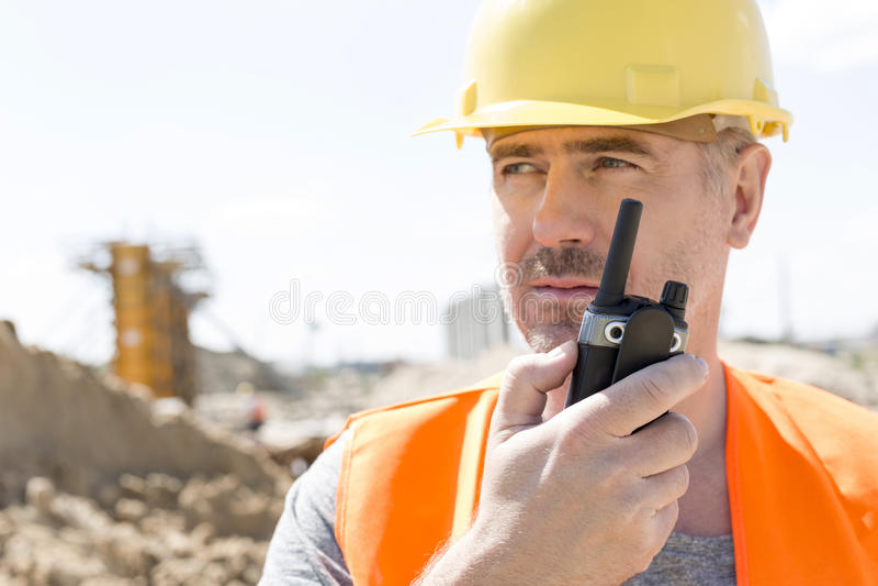 Уверенно заведущая используя рацию на строительной площадке стоковые фото