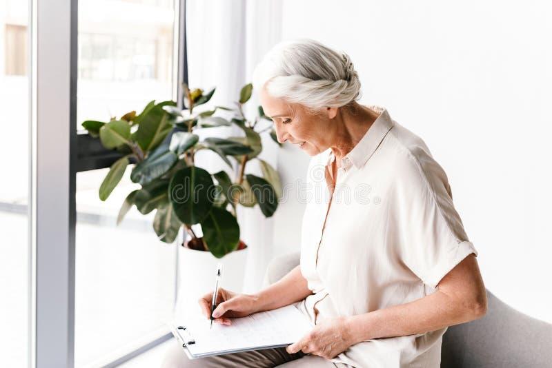 Уверенно зрелая бизнес-леди принимая примечания стоковое изображение