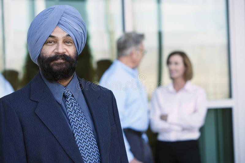 Уверенно индийский бизнесмен с коллегами позади стоковые изображения rf