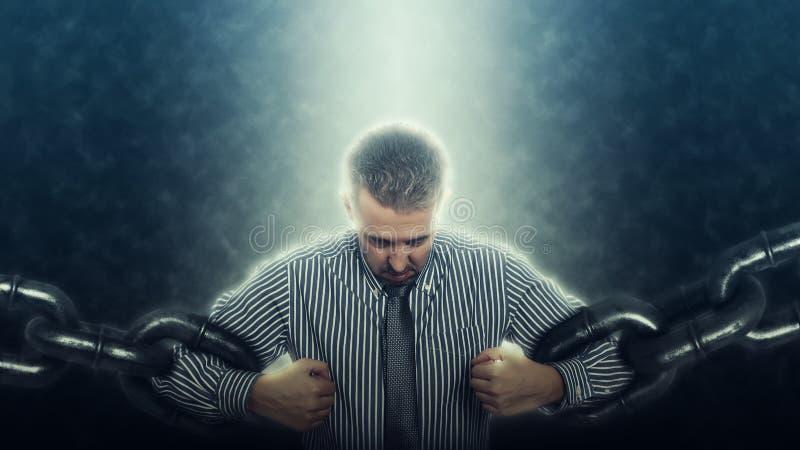 Уверенно и сердитый бизнесмен ломая цепь стоковое изображение