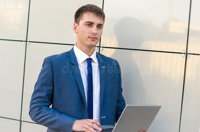Уверенно и успешный бизнесмен держа компьтер-книжку стоковое изображение rf