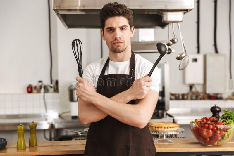 Уверенно кашевар шеф-повара молодого человека в рисберме стоковая фотография rf