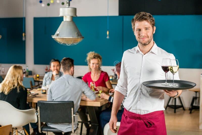Уверенно кельнер держа поднос на ресторане стоковое фото