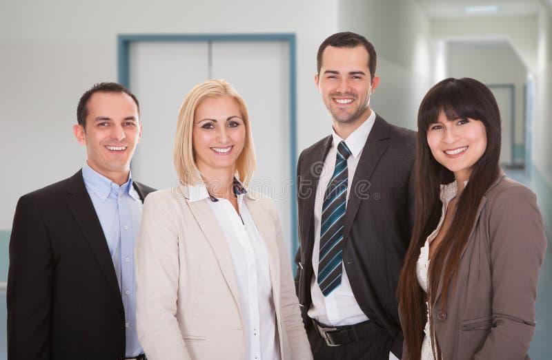 Уверенно команда дела усмехаясь в офисе стоковые фото
