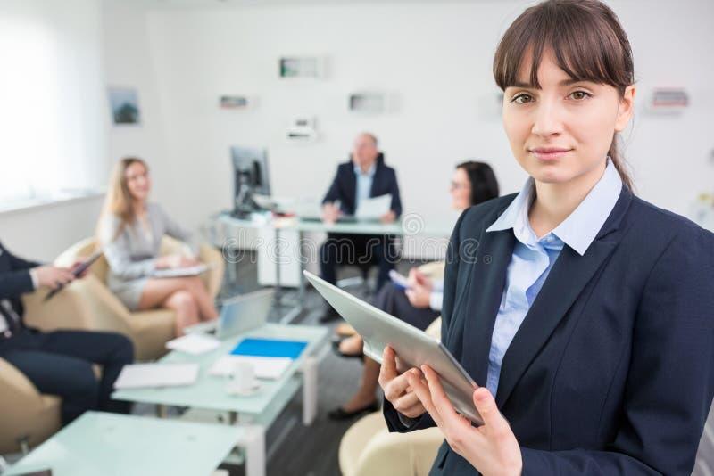 Уверенно коммерсантка держа таблетку цифров в конференц-зале стоковое изображение