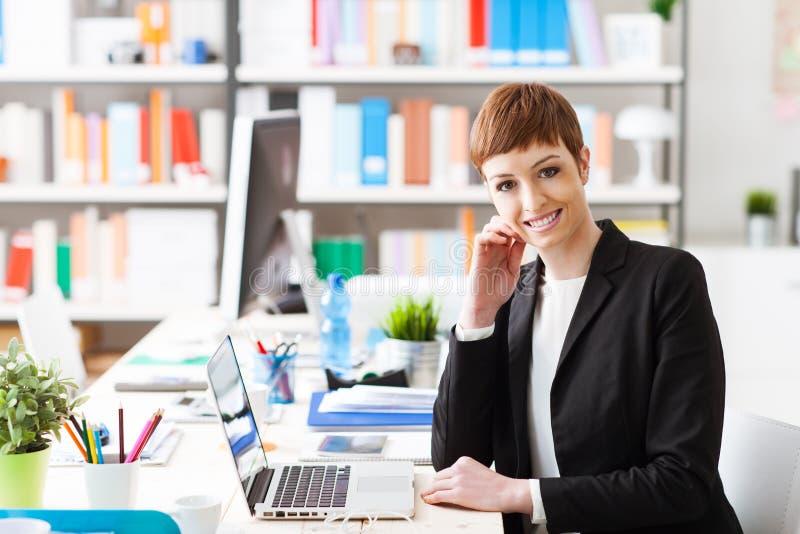 Уверенно коммерсантка представляя в ее офисе стоковые фото