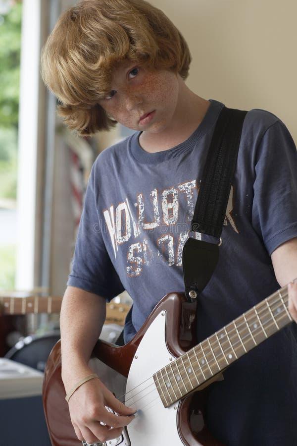 Уверенно мальчик играя гитару в гараже стоковые фотографии rf