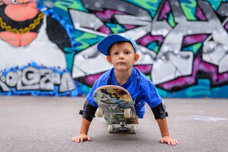 Уверенно мальчик играя на скейтборде стоковое изображение