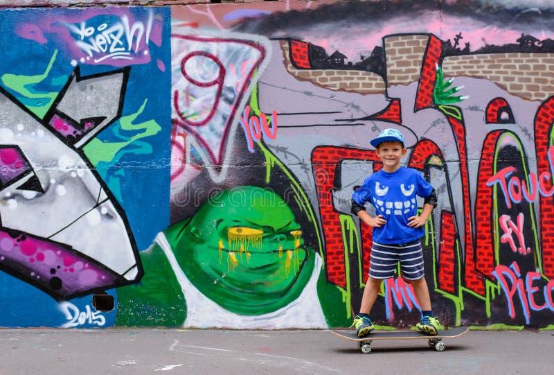 Уверенно мальчик представляя на его скейтборде стоковое изображение
