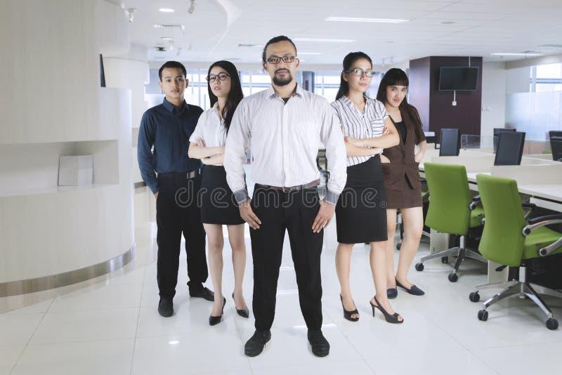 Уверенно менеджер стоя с его командой на офисе стоковое фото rf