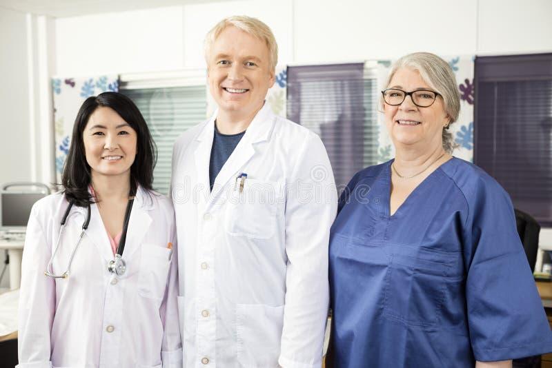 Уверенно медицинская бригада стоя совместно в клинике стоковые изображения