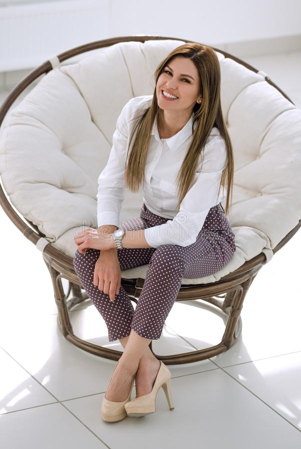 Уверенно молодая женщина сидя в мягком круглом стуле стоковые фотографии rf
