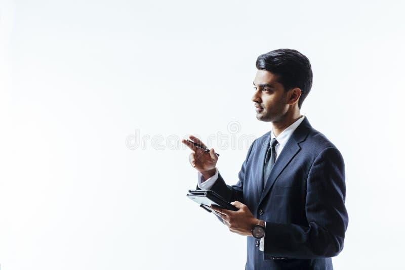 уверенно молодой человек в сочинительстве делового костюма на электронной таблетке стоковое изображение