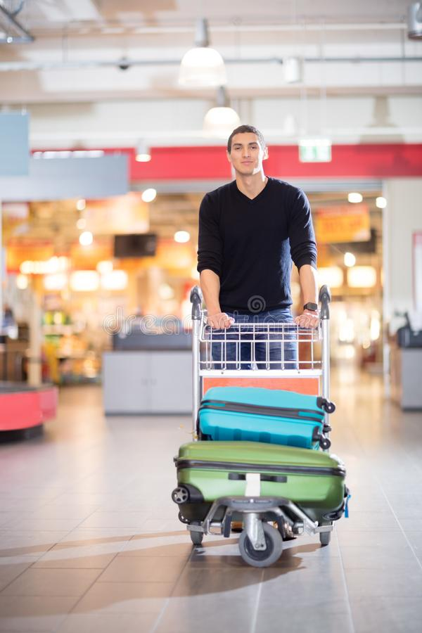 Уверенно молодой человек с багажом в тележке на авиапорте стоковая фотография