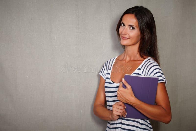 Уверенно молодая женщина держа беспроволочную таблетку стоковая фотография