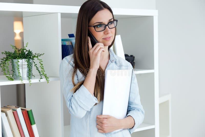 Уверенно молодая женщина работая в ее офисе с мобильным телефоном стоковое фото