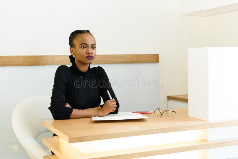 Уверенно молодая черная ручка удерживания бизнес-леди и думать на столе в офисе стоковая фотография