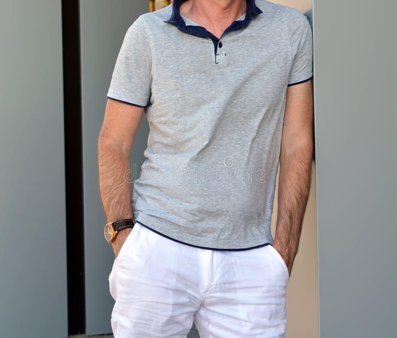 Уверенно молодой человек в рубашке и белом лете задыхается представлять около кирпичной стены стоковые фотографии rf