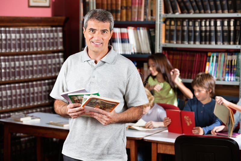 Уверенно мужской библиотекарь держа книги пока стоковая фотография
