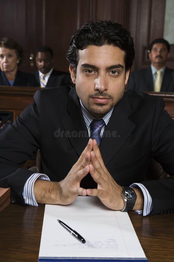 Уверенно мужской защитник сидя в зале судебных заседаний стоковые фотографии rf