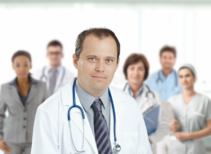 Уверенно мужской доктор перед медицинской бригадой стоковые фотографии rf