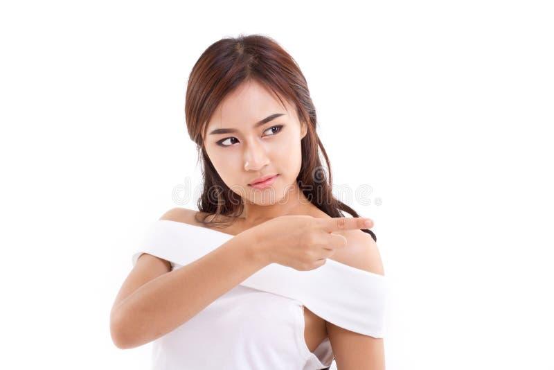 Уверенно, серьезная женщина указывает ее палец к пустому пространству над whit стоковое фото