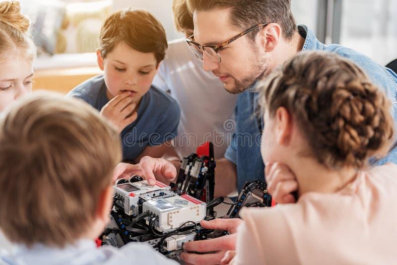 Уверенно серьезные люди изучая робот стоковые изображения