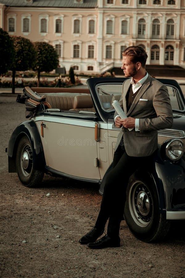 Уверенно состоятельный молодой человек с газетой около классического автомобиля с откидным верхом стоковые фото