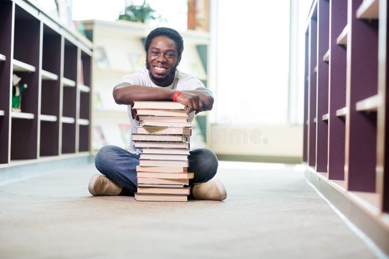 Уверенно студент при штабелированные книги сидя внутри стоковые фотографии rf