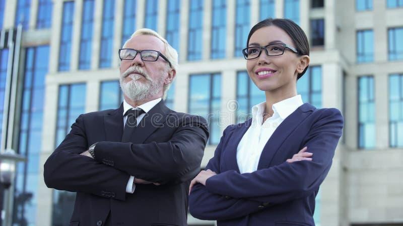 Уверенные достигшие возраста и молодые деловые партнеры с пересеченными оружиями около центра офиса стоковое фото rf